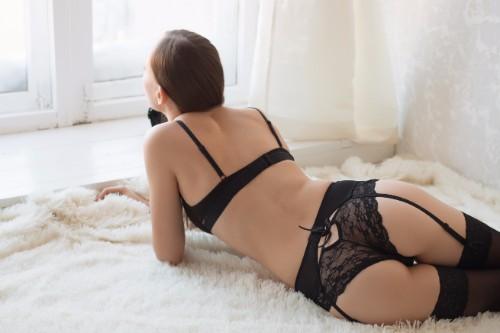 ベッドに寝そべり窓の外を見つめる下着姿の女性